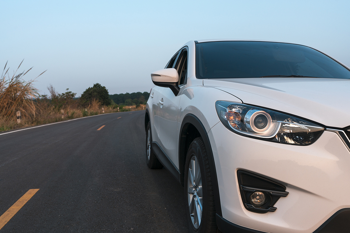 compact SUV car with sport and modern design parked on concrete road by the sea at sunset. Environmentally friendly technology. Business success concept.